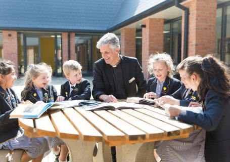 Prep pupils in play area facilities with headmaster of prep Father Chris